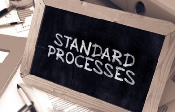 Standard Processes Handwritten on Chalkboard. Composition with Small Chalkboard on Background of Working Table with Ring Binders, Office Supplies, Reports. Blurred Background. Toned Image. 3D Render.