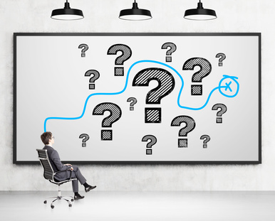 Businessman sitting on chair. Whiteboard with question marks and blue line in front. Concrete background. Concept of solving problem.