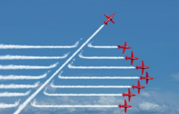 Game changer business or political change concept and disruptive innovation symbol and be an independent thinker with new industry ideas as an individual jet breaking through a group of airplane smoke as a metaphor for defiant leadership.