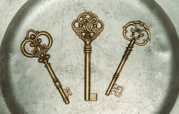 Three antique golden door keys on iron plate