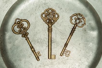 Three antique golden door keys on iron plate